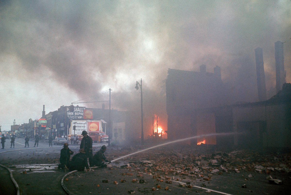 DETROIT, UNITED STATES - JULY 01:  Firemen are protected by police (from snipers, etc.) while they battle smoking blaze after race riots rock the city.  (Photo by Declan Haun/The LIFE Picture Collection/Getty Images)