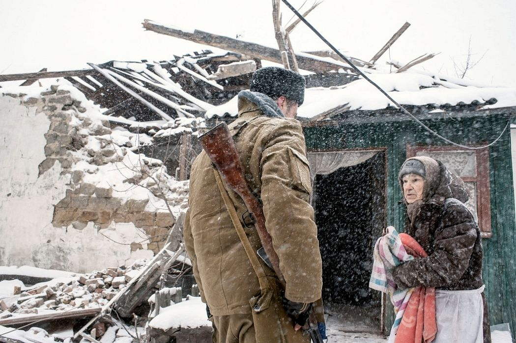 UKRAINE. Shahanov, East Ukraine. November 30, 2014. A young Cossack soldier greets 86-year old Cossack woman whose home had recently been destroyed by Ukrainian Army shelling in the separatist stronghold.