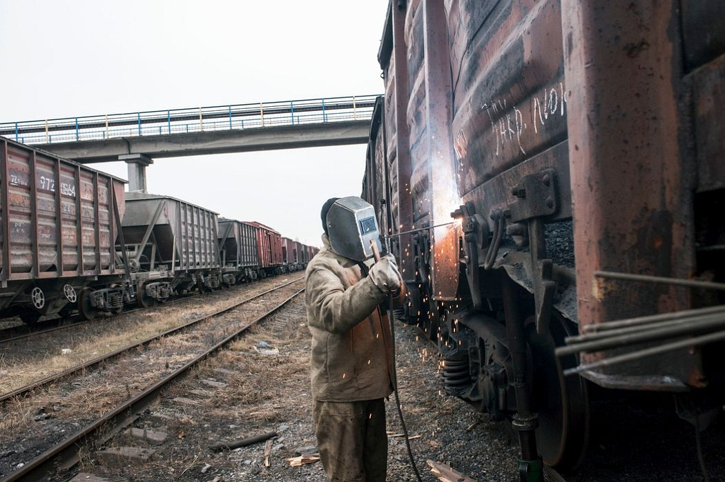 UKRAINE. Ilovaisk, East Ukraine. November 25, 2014. A welder repairs freight trains damaged by separatist shelling of a train yard when it was occupied by the Ukrainian army, in what is now a separatist strong hold.