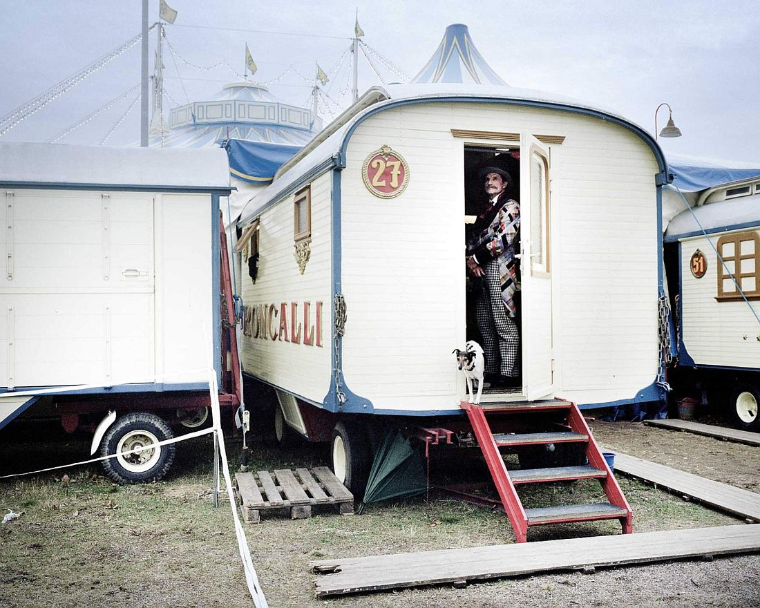 Dog trainer Leonid Beljakov with one of his dogs in front of his caravan.
