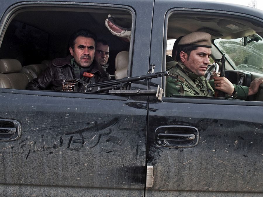 IRAQ. Dokuk, Kirkuk Province. December 3, 2014. Kurdish Peshmerga fighters drive through an Arab village recently captured from the Islamic State near the front line about 30Km south of the city of Kirkuk.