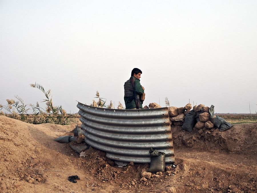 IRAQ. Dokuk, Kirkuk Province. December 3, 2014. A Kurdish peshmerga fighter mands a defensive position along the frontline against the Islamic State in the farmlands on the outskirts of Dokuk, a town about 30Km south of the city of Kirkuk.
