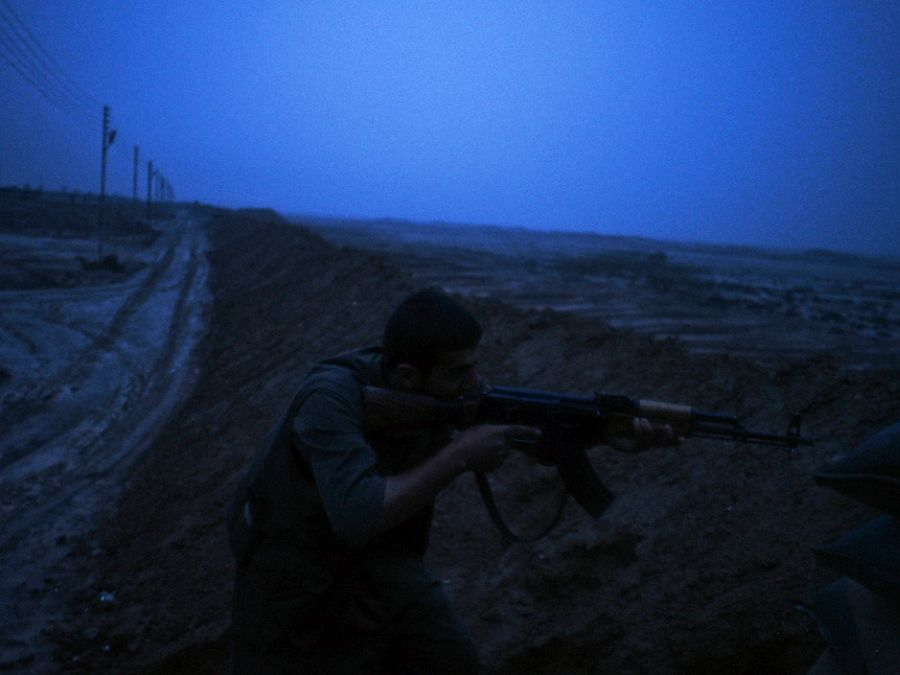 IRAQ. Dokuk. December 3, 2014. A Kurdish PKK fighter aims his rifle toward an Islamic State (IS) position during sporadic clashes in the front line near the village of Dokuk, about 35Km south to Kirkuk.