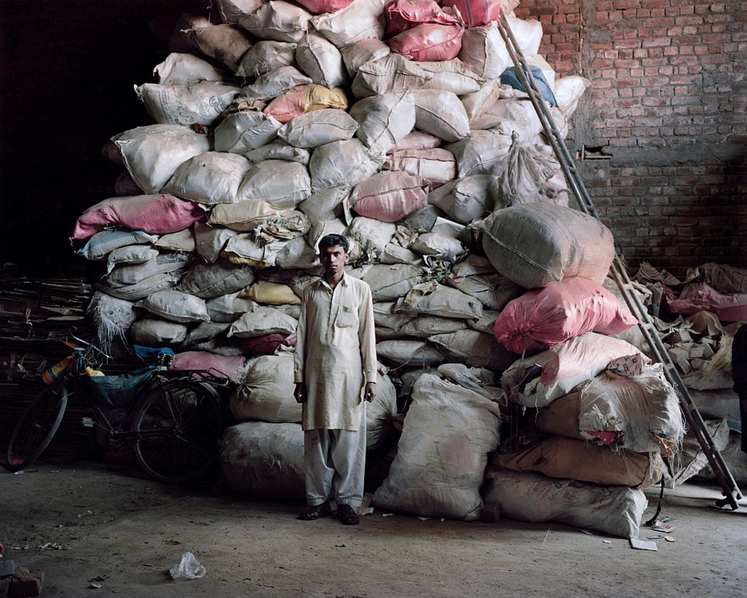 Lahore, Pakistan. A guy stand in front of a huge pile of electronic components which will be later processed to extract precious metals.