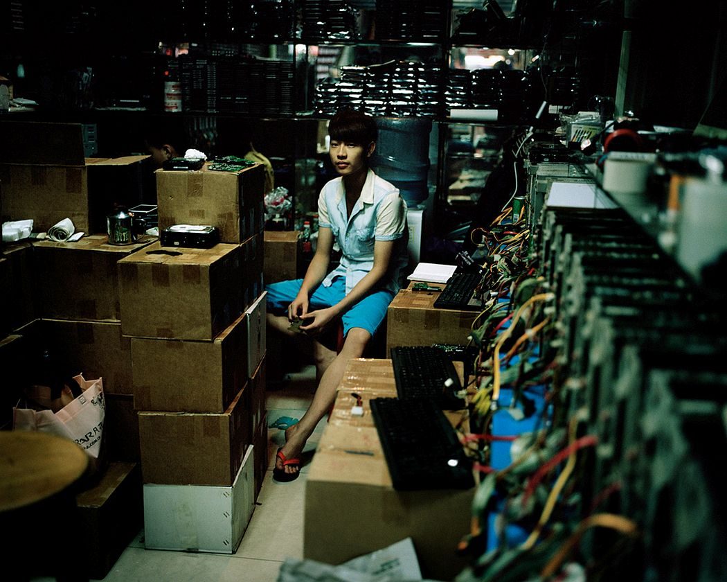 "Guangzhou, China A boy waits for customers in his hardware materials store, inside a big shopping mall for electronics. They sell mostly used materials which can then be used to compose ""new"" second-hand electronic items."