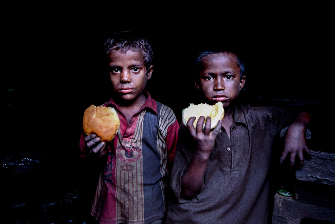 Two child worker taking lunch in the factory. The only clean thing about these children is the lunch he is eating.Dhaka, 2006