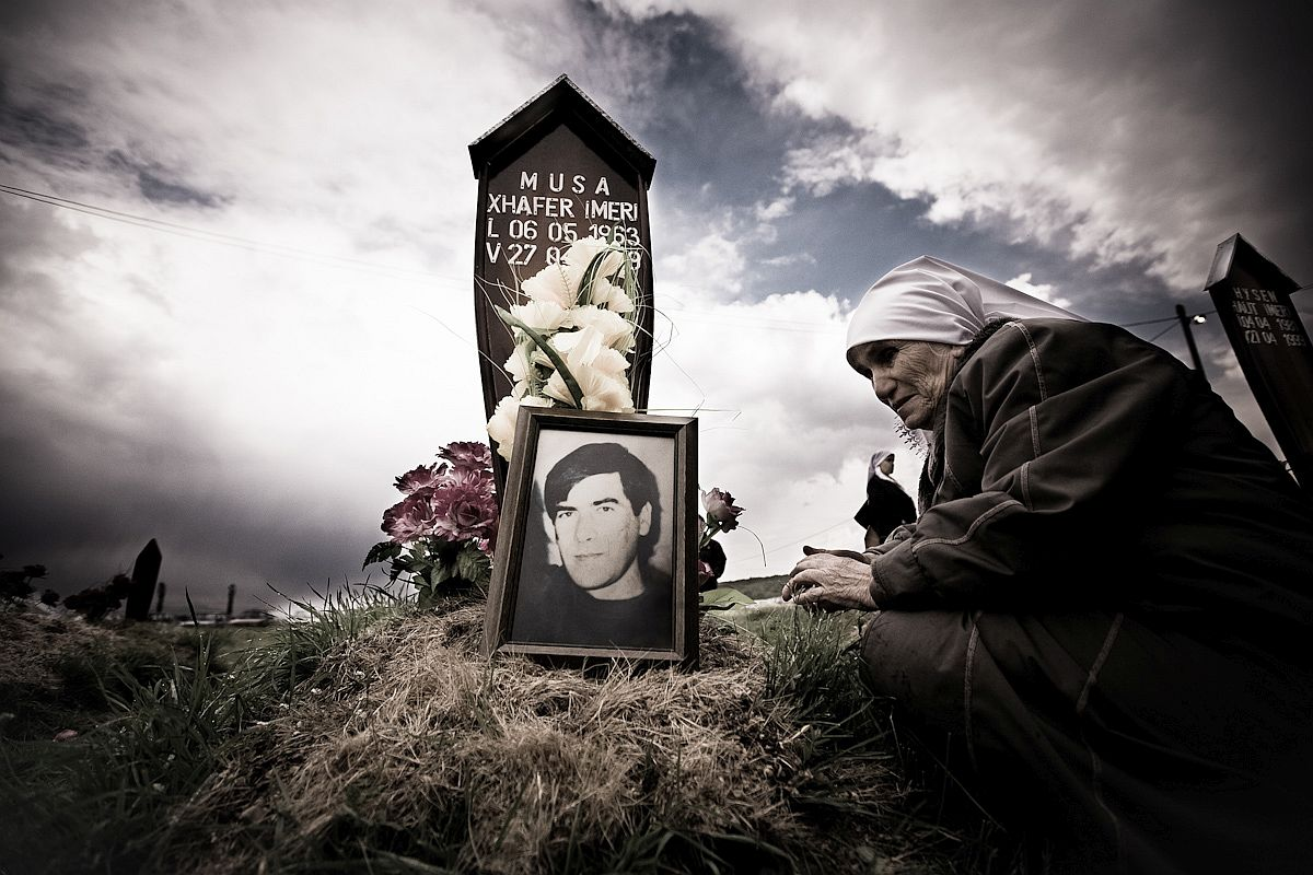 A Kosovar woman prays at the grave of her son was killed during the war. The son's body was found in a mass grave not far from Krusa e Madhe