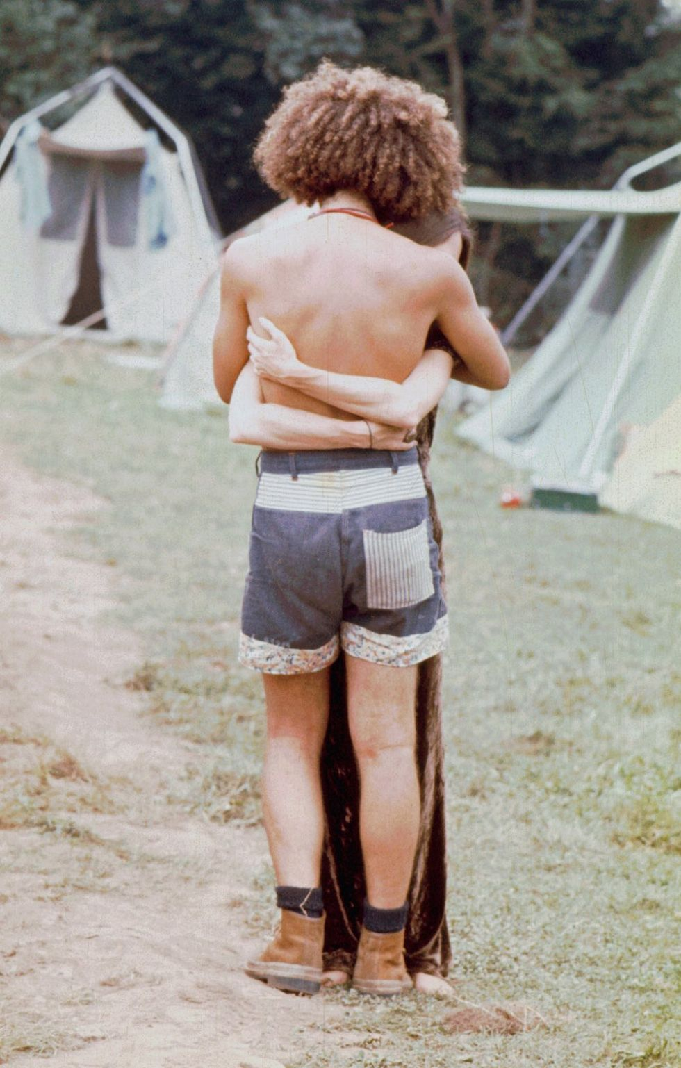 One of the dancers hugs someone on the dirt road as they stand near the tents.