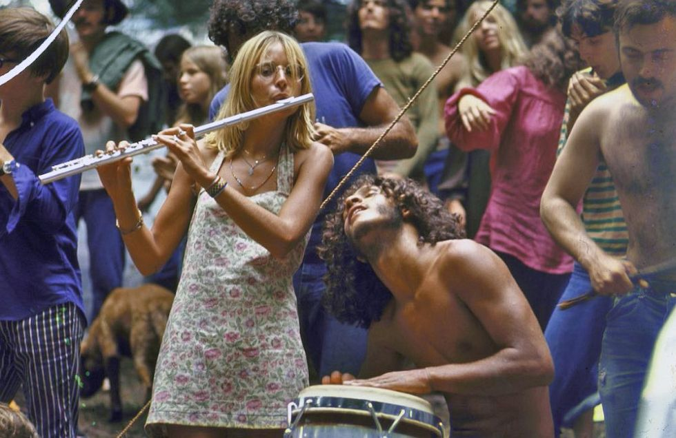 Shirtless male drummer & dress-wearing female flutist jamming