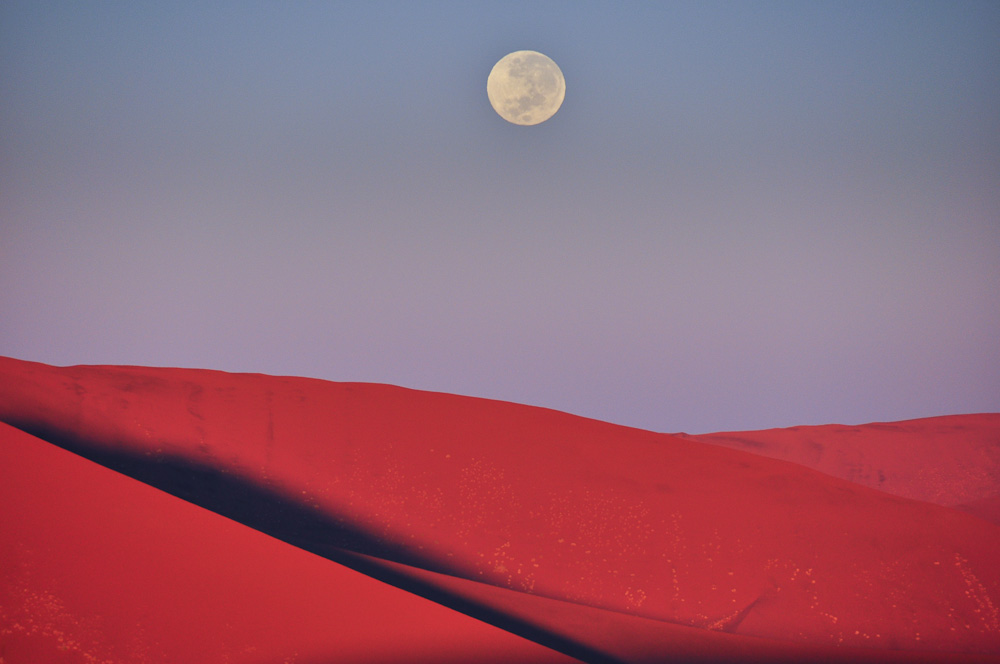 Moonrise over red dunes, Namibia