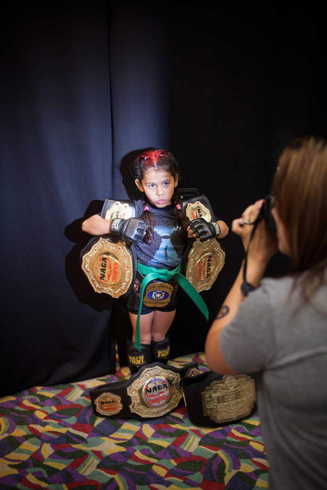 "Regina ""Black Widow"" Awana, 7, with her Championship belts, posing for her sponsor at United States Fight League(USFL) All-star Pankration show at Blue Water Casino in Parker, Arizona on 25th of October 2013. Photo: Miikka Pirinen"
