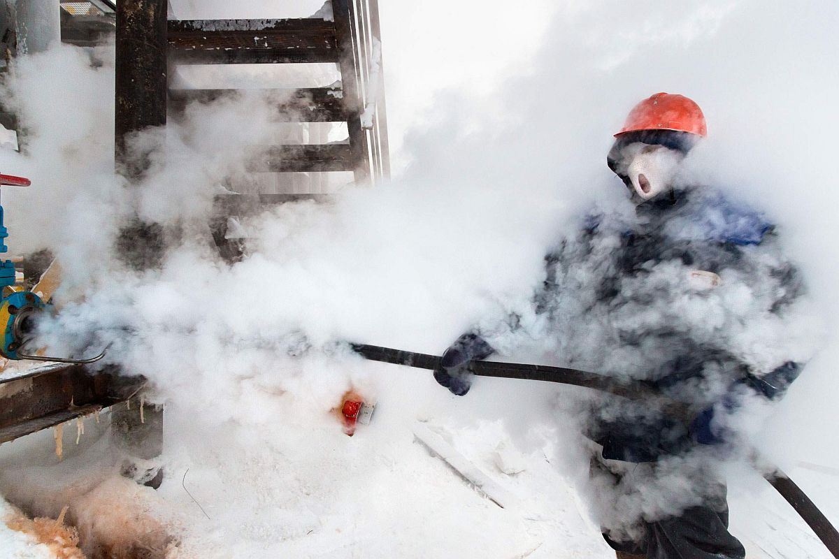 . A Russian gas worker sprays steam to unfreeze pipes in Novy Urengoi, Arctic Siberia, Russia, December 2014.